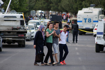 People react as they leave from the scene following a car bomb attack on a police vehicle in the Kurdish-dominated southeastern city of Diyarbakir