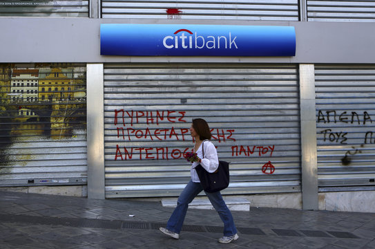 A woman with flowers walks past a bank after a May Day protest in central Athens