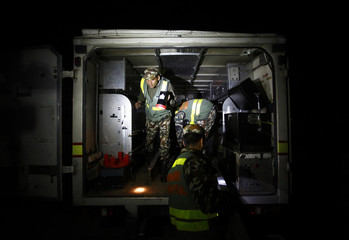 Members of a bomb disposal team from the Nepalese Army work inside their vehicle after detonating a suspected bomb that was planted at a bus station in Kathmandu