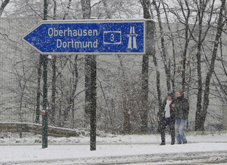 A couple walks near an exit of the A3 motorway near the western German city of Leverkusen