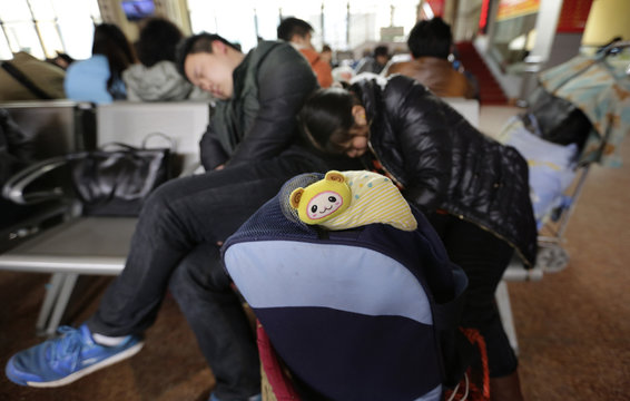 A couple sleep next to their bag as they wait for a train at Zhengzhou Railway Station