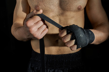 Closeup of a body combat athlete applying tape on the hands.