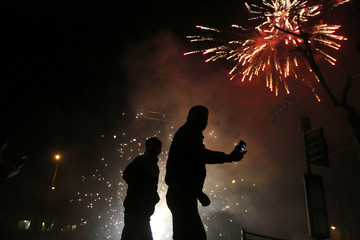 A man tries to take a pictures with his mobile phone as residents set off fireworks as part of Chinese New Year celebrations in Shanghai