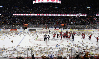 Calgary Hitmen players are surrounded by Teddy Bears thrown on the ice at the Hitmen Teddy Bear toss during their major junior hockey game against the Kootenay Ice in Calgary.