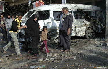 Residents walk past a damaged vehicle at the site of a bomb attack in Baghdad
