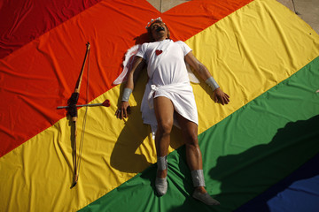 Mario Almeida, a 36-year-old Brazilian gay activist dressed up as Cupid, lies on a heart-shaped cloth with rainbow colours during a protest in Malaga, southern Spain