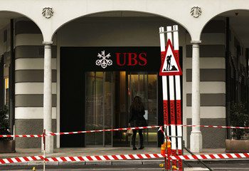 A woman woman walks past a construction road sign in front of a branch of Swiss Bank UBS in Lugano