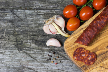Top view of the old wooden desk with hot sausage Chorizo, tomatoes, the half of garlic bulb and a clove of garlic.  Free place for your text is at the left side of the photo.