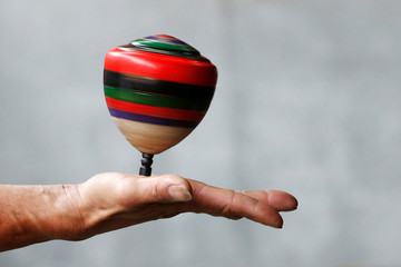 A spinning top is seen on a hand during a performance at Sanxia old street in New Taipei City