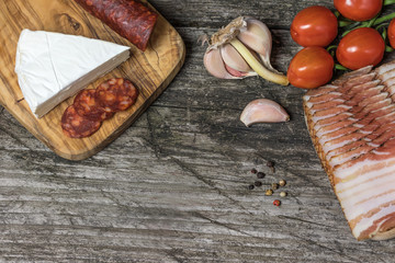 Top view of the old wooden desk with hot sausage Chorizo, tomatoes, garlic bulb and a piece of the Petite Brie cheese.