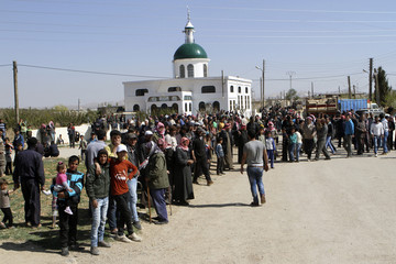 Lebanese residents wait to greet the arrival of Lebanese Army troops at Tfail village in the Bekaa Valley