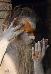 A Hindu holy man applies paint on his forehead at Pashupati Temple in Kathmandu