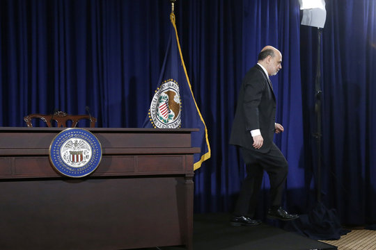 Bernanke steps down from the stage as he departs at the end of his final planned news conference before his retirement, at the Federal Reserve Bank headquarters in Washington
