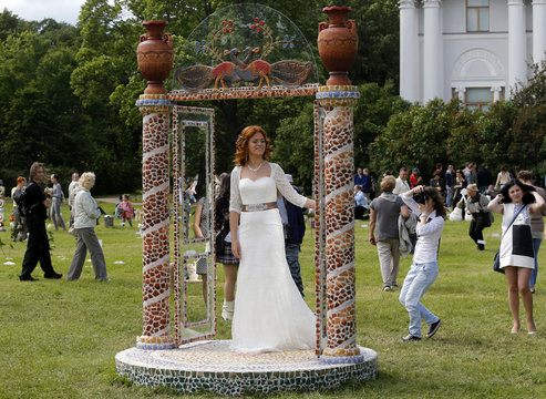 """A bride stands in a structure called """"Gates of the Maze"""" during the """"Glass and Ceramics in the Landscape"""" in central park in St. Petersburg"""