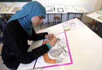 A student draws a cartoon depicting embattled Libyan leader Muammar Gaddafi, at Fatma al-Zahraa school in Benghazi