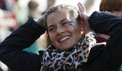 A spectator with the Scottish flag painted on her cheek watches the action at the annual Braemar Highland Gathering in Braemar, Scotland