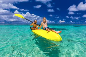 Two young caucasian boys kayaking at tropical sea on yellow kayak