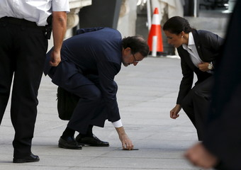 Spain's PM Rajoy picks up his fallen mobile phone as he arrives at Parliament to attend budget 2016 debate in Madrid