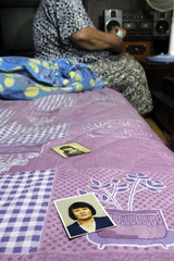 Old photographs of Cho, are seen on a bed whilst she describes her life as a prostitute serving U.S. military personnel stationed in South Korea, in her room in Pyeongtaek