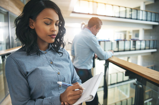 Young black woman thinking over notepad in office
