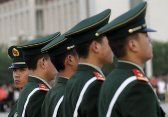 Paramilitary policemen stand guard during a flag-lowering ceremony at Beijing's Tiananmen Gate Square Square