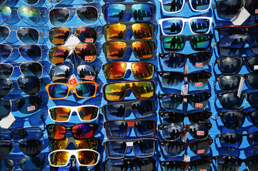 A vendor and Reuters photographers Tony Gentile and Damir Sagolj are reflected in sunglasses offered for sale on a beach in Recife