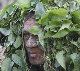 A devotee, covered with fresh leaves, attends a holy mass celebrating the feast day of their patron Saint John the Baptist in the village of Bibiclat