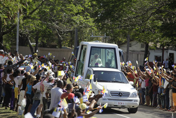 People wave flags while Pope Benedict XVI is being driven around the streets of Santiago de Cuba