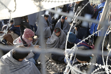 Migrants rest next to a border fence at the Greek-Macedonian border