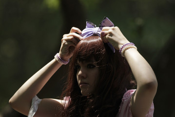 """A member of the """"Lolitas Paradise"""" club adjusts her headband in a park in Monterrey"""
