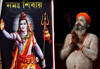 A Sadhu or a Hindu holy man, smeared with ash, offers prayer to the Sun god next to a picture of the Hindu Lord Shiva at a makeshift shelter in Kolkata