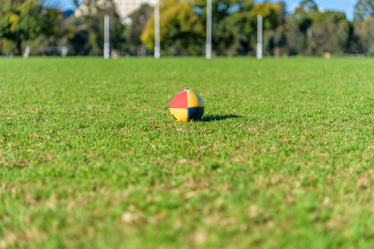 A single close football on a field with a set of Australian Football League goal posts in the background in Melbourne Australia. Presented in a shallow depth of field.