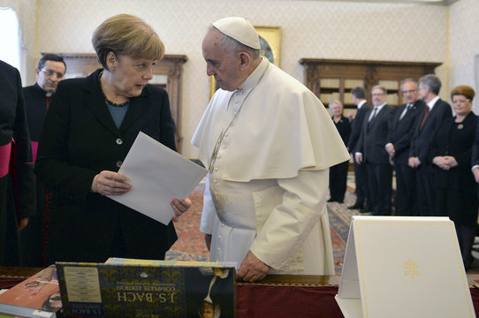German Chancellor Angela Merkel exchange gifts with Pope Francis during a private audience at the Vatican