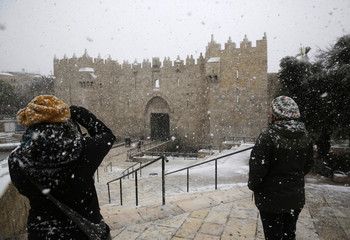 A woman takes pictures during snowfall in winter near Damascus Gate outside Jerusalem's Old City