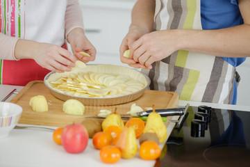hands of people preparing apple tart
