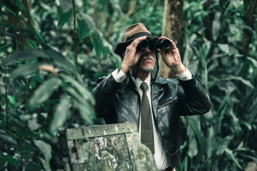 Explorer looking with binoculars standing in bush next to car wreckage.