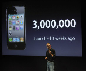 Apple CEO Jobs holds an iPhone 4 during a news conference at Apple headquarters in Cupertino, California