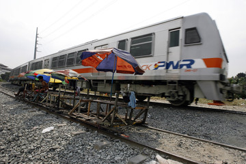 A Philippine National Railways train moves past a wooden makeshift train parked to receive passengers along a railway line in Manila