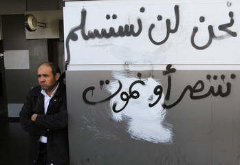 "A man stands by graffiti which reads ""we will not give up, we win or we die"" in downtown Tripoli"