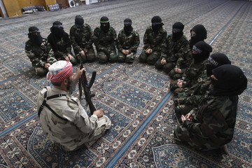Female members of the Ahbab Al-Mustafa Battalion sit around their leader Abu al-Taib during military training in a mosque in the Seif El Dawla neighbourhood in Aleppo