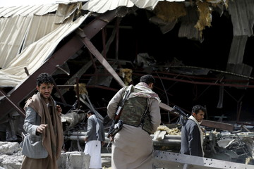 Houthi militants inspect damage at a fabric factory after a Saudi-led air strike hit it in Yemen's capital Sanaa
