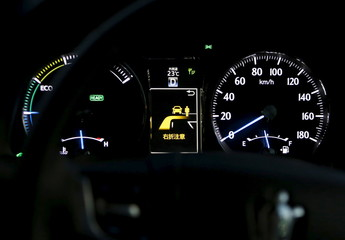 An onboard display between speed meters shows a right turn collision caution as a staff member of Toyota Motor Corp drives its latest model of Toyota Crown equipped with the ITS technology in Tokyo