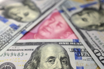 Benjamin Franklin U.S. 100-dollar banknotes and a Chinese 100-yuan banknote depicting the late Chinese Chairman Mao Zedong, are seen in a picture illustration in Beijing