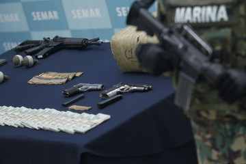 Guns and money seized from Velasquez, a suspected drug leader of the Zetas drug cartel, are pictured before Velasquez is presented to the media in Mexico City