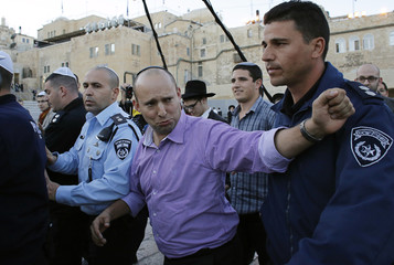 Naftali Bennett, leader of the Bayit Yehudi party, gestures as he leaves the Western Wall in Jerusalem's Old City