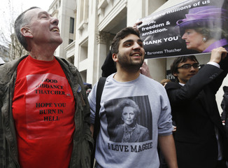 An anti-Thatcher demonstrator he stands next to supporters of the former prime minister following her funeral service at St Paul's Cathedral in London
