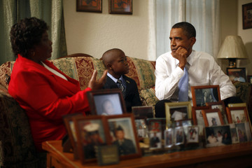 U.S. President Barack Obama listens to Maude Smith and her grandson David Robichaux Jr. in their home in the Columbia Parc Development in New Orleans