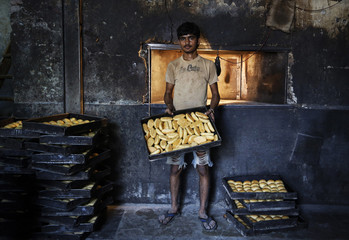 Sameer poses inside a bakery at a slum in Mumbai
