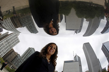 Former Illinois Senate candidate Stefanie Linares, who is a lawyer, is reflected in the Cloud Gate Sculpture as she poses for a photo in Chicago, Illinois