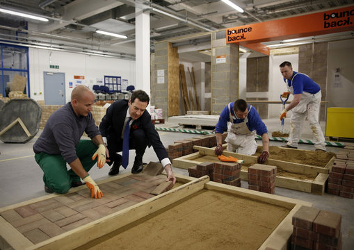 Britain's Chancellor George Osborne lays a brick in block paving demonstration during a tour of Brixton Prison in London